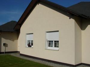 Rolety napůl stažené na oknech domu.