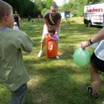 Dítě mělo skákat v pytli, ale nešlo mu to. Tak ho dobrovolnice odnáší do cíle v pytli.