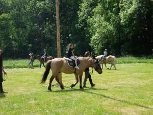 Děti jezdí na koních a zkušení jezdci je vodí ve velkém kruhu