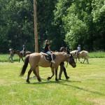 Děti jezdí na koních ve velkém kruhu, koně vedou zkušení jezdci